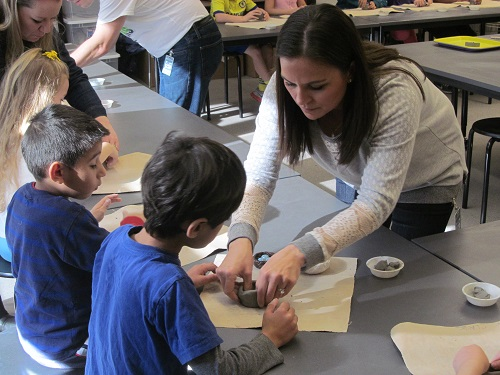 A volunteer Art Docent helps students make clay bird nests.